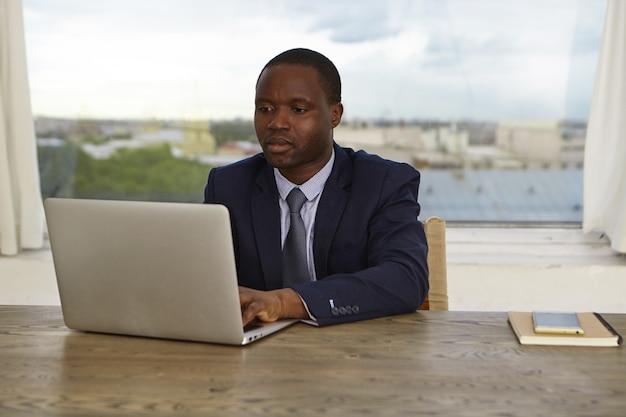 Zdjęcie poważnego, skoncentrowanego, ciemnoskórego pracownika biurowego w formalnym stroju, zajętego, skoncentrowanego, używającego zwykłego laptopa do pracy, sprawdzającego pocztę e-mail lub sporządzającego raport. praca ludzi i technologia