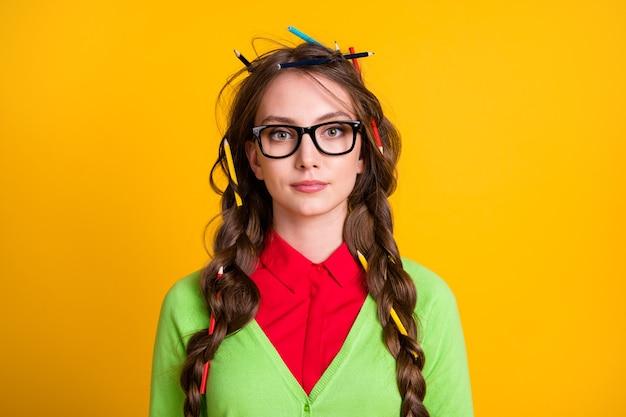 Zdjęcie poważnej dziewczyny z niechlujną fryzurą nosi strój w stylu maniaka na białym tle na żółtym tle