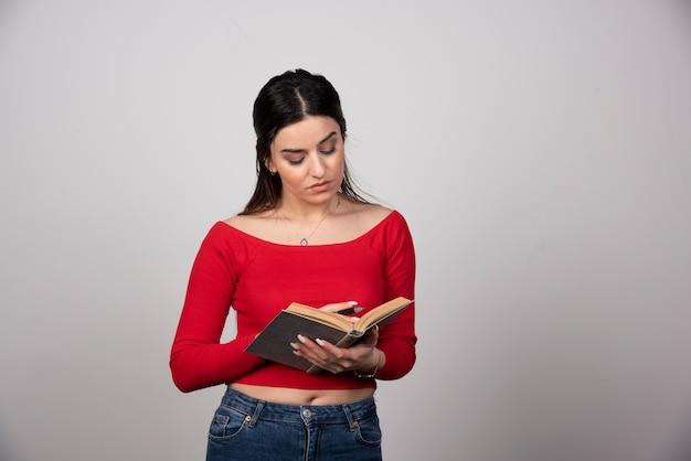 Zdjęcie poważnej kobiety czytającej książkę i trzymającej ołówek.