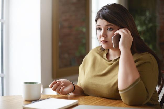 Zdjęcie poważnej młodej kobiety rasy kaukaskiej plus size mówiącej na smartfonie siedzącej przy stoliku kawiarnianym przed otwartym zeszytem i kubkiem, zmartwiona spojrzeniem, zdenerwowana negatywnymi wiadomościami. selektywna ostrość