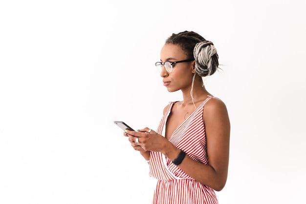 Zdjęcie poważnej młodej kobiety z dredami pozowanie na białym tle przy użyciu telefonu komórkowego na czacie.