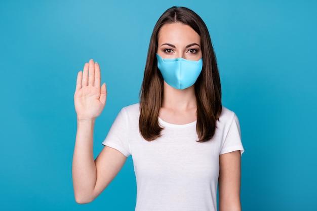 Zdjęcie poważnej, pewnej siebie dziewczyny, trzymaj rękę, powiedz, że zatrzymaj gest szerząca się infekcja nosicielska nosić dobry wygląd maski medycznej na białym tle nad niebieskim kolorem tła