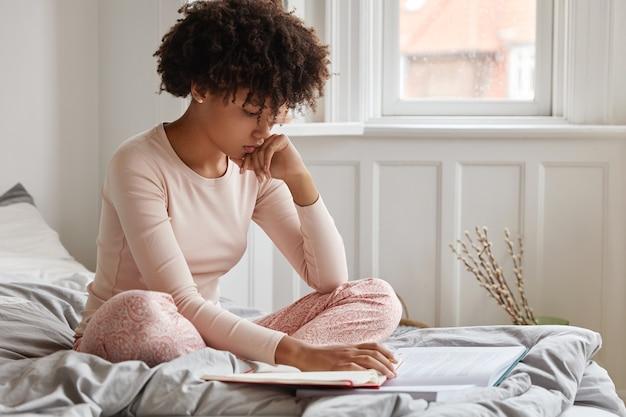 Zdjęcie poważnej, skoncentrowanej, ciemnoskóra młoda kobieta nosi bieliznę, siedzi w pozycji lotosu na łóżku, uczy się materiału z książki i zeszytu,