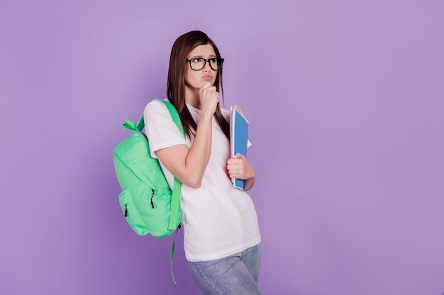Zdjęcie poważnej studentki, która myśli, że trzymaj torbę zeszytów na białym tle fioletowym tle