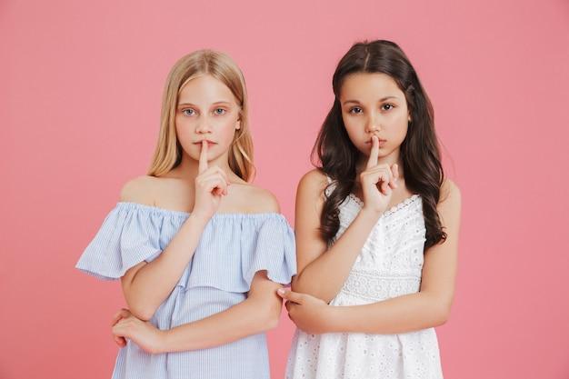 Zdjęcie poważnych małych dziewczynek w wieku 8-10 lat ubranych w sukienki, trzymających palec wskazujący na ustach i proszących o milczenie, odizolowane na różowym tle
