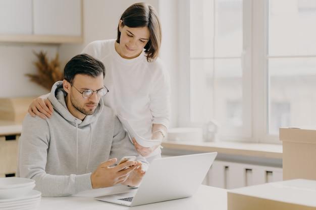 Zdjęcie powiadomienia o studium męża i żony z banku, trzyma telefon komórkowy i dokumenty, pracuje na komputerze przenośnym, pozuje w kuchni podczas dnia relokacji, ubrany w zwykłą odzież, oszczędza pieniądze