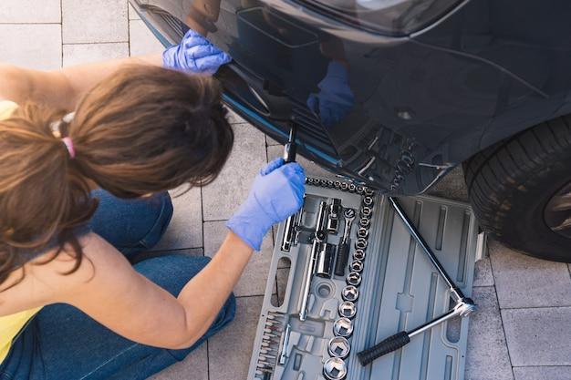 Zdjęcie powyżej przedstawiające kasztanowatą mechanikę naprawiającą samochód śrubokrętem i pudełkiem kluczy nasadowych