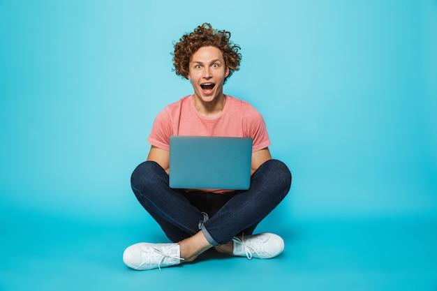Zdjęcie pozytywnego faceta z brązowymi kręconymi włosami za pomocą srebrnego laptopa, siedząc na podłodze ze skrzyżowanymi nogami
