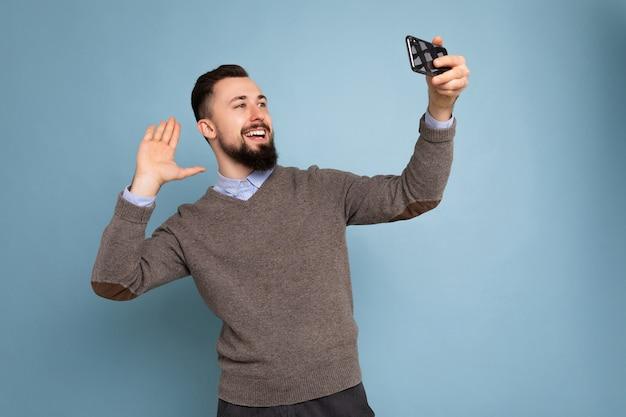 Zdjęcie pozytywnego, przystojnego, młodego, nieogolonego mężczyzny z brodą, ubrany w szary sweter i