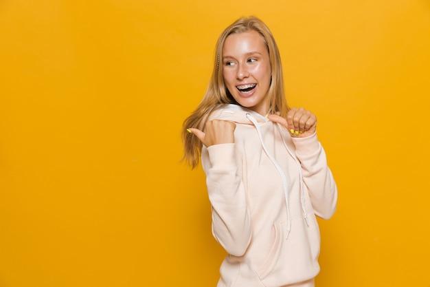 Zdjęcie pozytywnej dziewczyny 16-18 lat z aparatem ortodontycznym wskazującym palec do tyłu na copyspace, odizolowane na żółtym tle