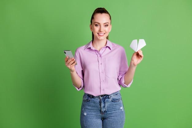 Zdjęcie pozytywnej dziewczyny trzymaj biały papierowy samolot użyj smartfona wyślij pocztę społecznościową nosić fioletową liliową koszulę dżinsowe dżinsy na białym tle nad zielonym kolorem tła