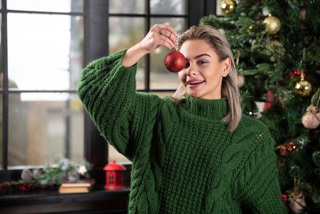 Zdjęcie pozytywnej dziewczyny trzymającej świąteczną czerwoną piłkę