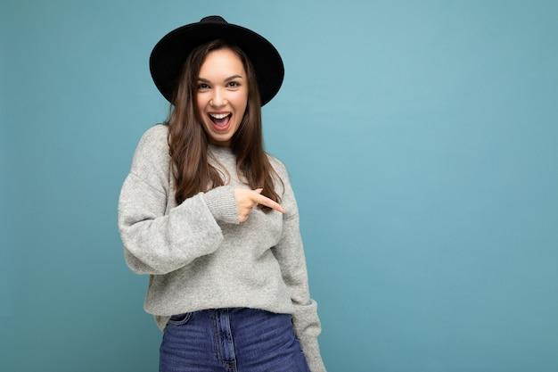 Zdjęcie pozytywnej młodej kobiety kierując palec na bok z pustą przestrzenią