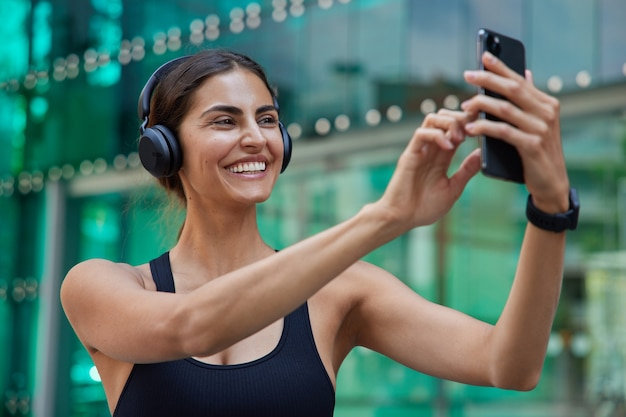 Zdjęcie pozytywnej sportsmenki w dobrej kondycji fizycznej nosi sportowe ubranie sprawia, że wideokonferencja przez smartfona słucha muzyki przez słuchawki ma trening na świeżym powietrzu na niewyraźne