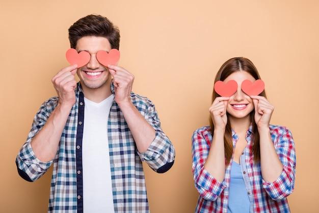 Zdjęcie pozytywnej uroczej czerwonej rudowłosej miłej, swobodnej uroczej pary dwóch osób trzymających walentynkowe pocztówki z rękami zakrywającymi oczy na białym tle na beżowym pastelowym kolorze