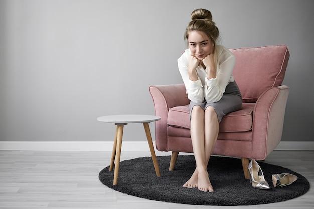 Zdjęcie pozytywnej uroczej młodej europejskiej bizneswoman w eleganckich, formalnych strojach, siedzącej w fotelu z bosymi stopami na dywanie w domu, uśmiechającej się tajemniczo, opierającej brodę na rękach