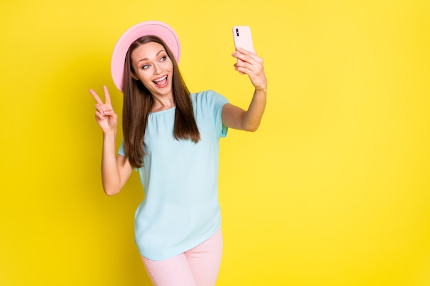 Zdjęcie pozytywnej wesołej dziewczyny ciesz się podróżą weź selfie inteligentny telefon spraw, aby znak v nosić niebieski różowy t-shirt spodnie spodnie kapelusz przeciwsłoneczny na białym tle nad jasnym połyskiem kolor tła