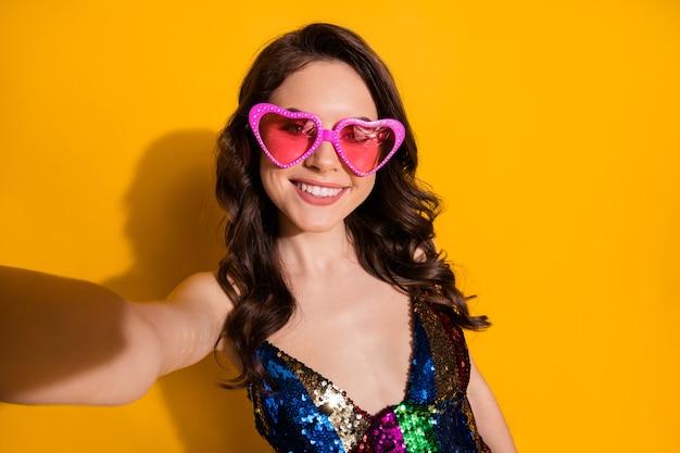 Zdjęcie pozytywnej wesołej dziewczyny sprawia, że selfie w letnie weekendy nosi spódnicę w kształcie serca okulary na białym tle nad jasnym połyskiem koloru tła
