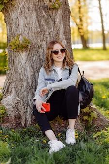 Zdjęcie pozytywnej, wesołej nastolatki spędzającej czas w parku przy korzystaniu z telefonu komórkowego.