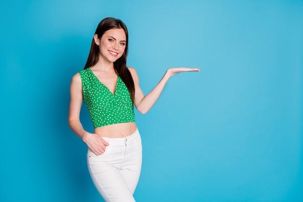 Zdjęcie pozytywnej, wesołej promotorki dziewczyny, trzymaj rękę, prezentuj opcję sprzężenia zwrotnego, reklamy, noś dobry strój, na białym tle na niebieskim tle