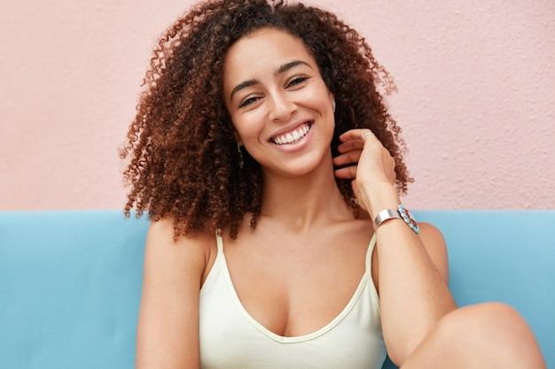Zdjęcie pozytywnie uśmiechniętej kobiety z szerokim, czarującym uśmiechem, ubranej niedbale i odpoczywającej w domu, czuje się zrelaksowana i wygodna