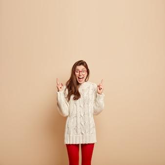 Zdjęcie pozytywnie uszczęśliwionej kobiety trzyma szeroko otwarte usta, krzyczy z podniecenia, wskazuje w górę wolną przestrzeń, ubrana w biały sweter, przezroczyste okulary, odizolowane na beżowej ścianie