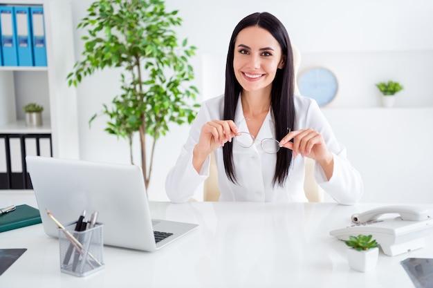 Zdjęcie profesjonalnego lekarza dziewczyny siedzieć przy stole w biurze szpitala