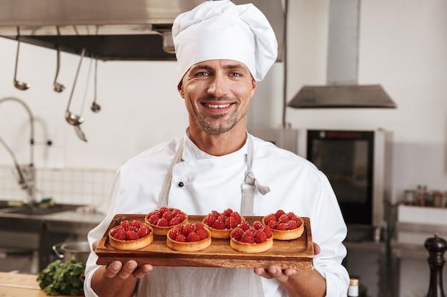 Zdjęcie profesjonalnego męskiego szefa w białym mundurze, trzymając talerz z ciastami