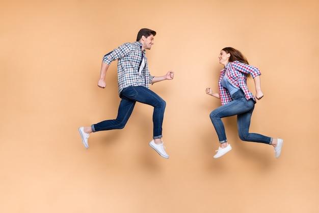 Zdjęcie profilowe całego ciała dwóch osób podekscytowanych pani facet skaczącej wysoko naprzeciw pędzących męskich sklepów damskich noszą zwykłe ubrania na białym tle na beżowym tle