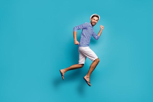 Zdjęcie profilowe całego ciała funky aktywnego faceta turystyczny skaczący w pośpiechu niskie ceny odzież na zakupy w paski marynarska koszula kamizelka czapka spodenki japonki na białym tle niebieski kolor
