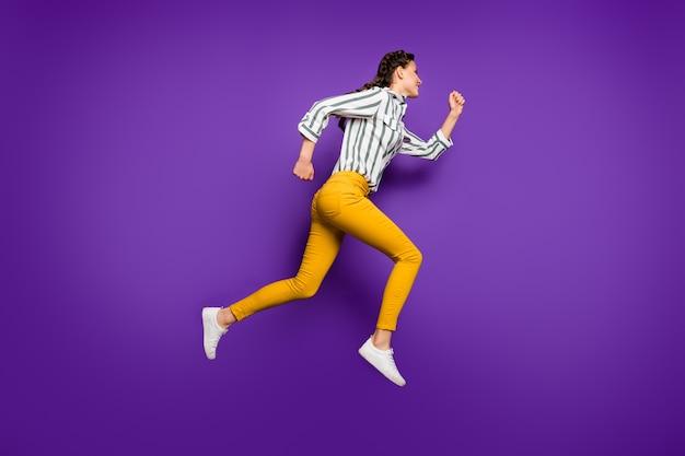 Zdjęcie profilowe całego ciała ładnej pani skaczącej w zawrotnym tempie ceny sprzedaży z rabatem zakupy nosić koszulę w paski żółte spodnie na białym tle fioletowy kolor