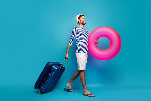 Zdjęcie profilowe całego ciała przystojnego faceta podróżnik na kółkach trzymaj duże różowe koło ratunkowe chcę zobaczyć oceaniczną marynarkę w paski koszula czapka szorty klapki japonki na białym tle niebieski kolor