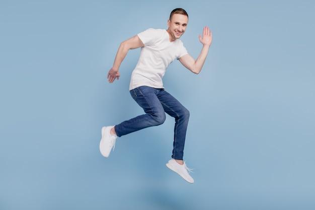 Zdjęcie profilowe całego ciała wesołego brązowowłosego atrakcyjnego mężczyzny skaczącego biegającego machającego witam na białym tle nad niebieskim kolorem tła
