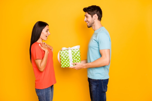 Zdjęcie profilowe dwóch facetów pani ludzi trzymających się za ręce duże pudełko na prezent romans niespodzianka na 8 marca nosić na co dzień modne niebieskie pomarańczowe koszulki dżinsy na białym tle żółty kolor ściana