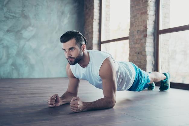 Zdjęcie profilowe faceta sportowca macho robi deskę na łokciach ręce pochylona podłoga zdeterminowana odzież sportowa podkoszulek spodenki tenisówki dom treningowy okna w pomieszczeniu