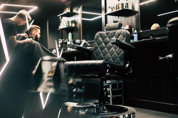 Zdjęcie profilowe młodego fryzjera przycinającego włosy klienta golarką elektryczną i grzebieniem w zakładzie fryzjerskim.
