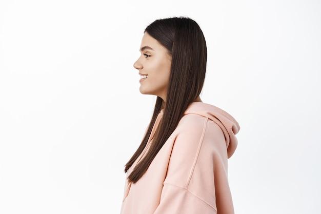 Zdjęcie profilowe młodej brunetki o świeżej, czystej skórze i długich włosach, patrzącej w lewo na miejsce, stojącej na tle białej ściany