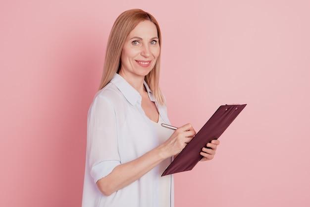 Zdjęcie profilowe młodej kobiety biznesu szczęśliwy pozytywny uśmiech trzymać schowek pisać notatki izolowane nad różowym kolorem tła