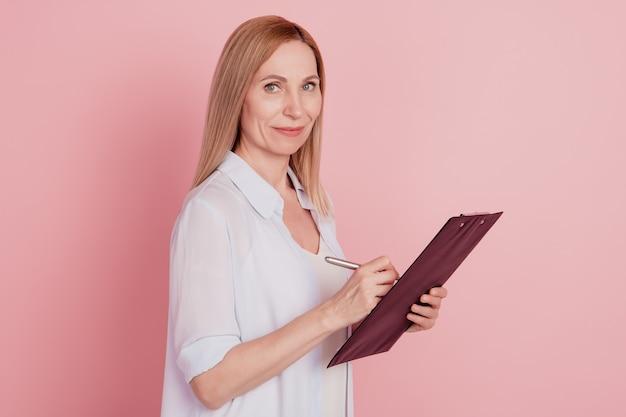 Zdjęcie profilowe młodej, pewnej siebie kobiety biznesu, aby wywiad hr przytrzymaj schowek na białym tle nad różowym kolorem tła