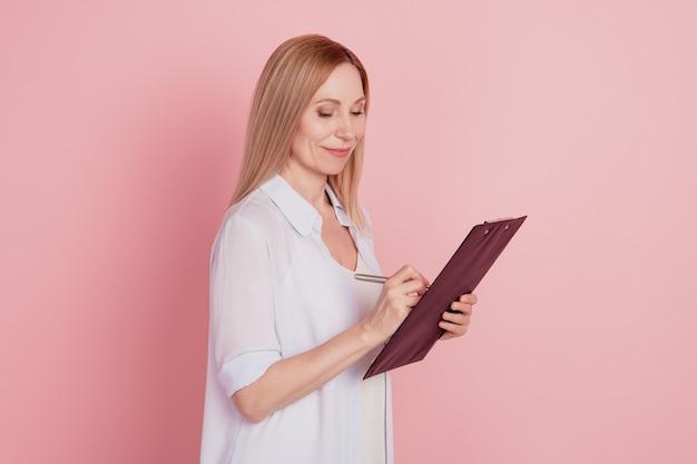 Zdjęcie profilowe młodej, pewnej siebie kobiety biznesu, wygląd, pisanie notatek, plan schowka na białym tle nad różowym kolorem tła
