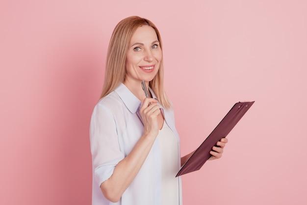 Zdjęcie profilowe młodej wesołej kobiety biznesu szczęśliwego pozytywnego uśmiechu trzymaj schowek myślę na białym tle nad różowym kolorem tła