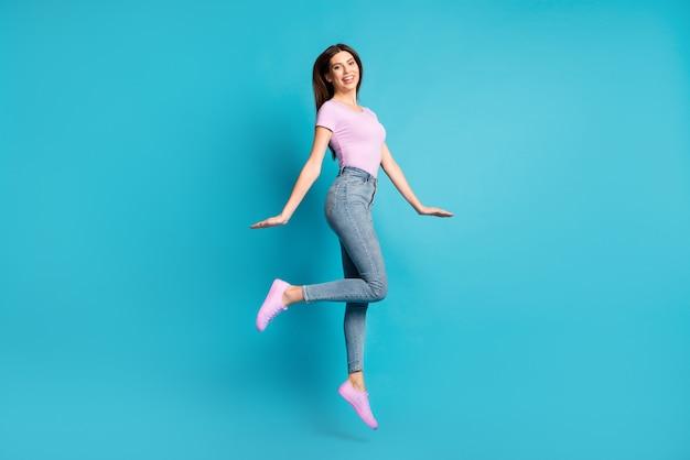 Zdjęcie profilowe na całej długości uroczej młodej dziewczyny skok nosić różowy t-shirt obuwie dżinsy izolowane niebieski kolor tła