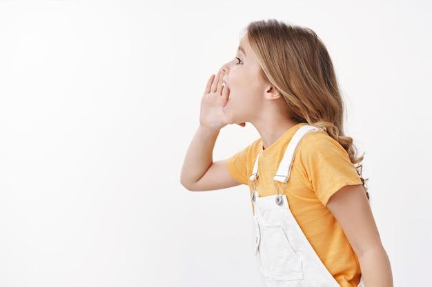 Zdjęcie profilowe naenergetyzowana zabawna urocza charyzmatyczna mała dziewczynka, dziecko dzwoniące do przyjaciela, krzyczące trzymaj rękę w pobliżu otwartych ust, krzycz głośno imię rodzica, szukaj ojca, szukaj kogoś, biała ściana