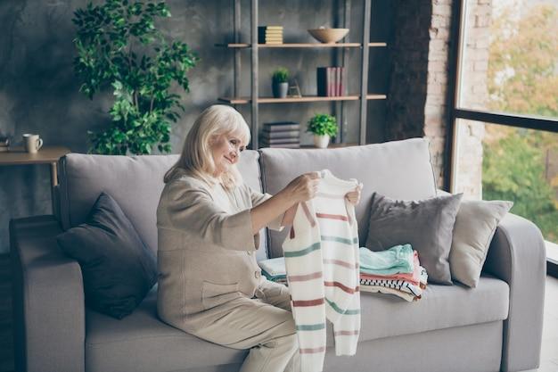 Zdjęcie profilowe niesamowitej siwowłosej starszej babci trzymającej schludny sweter w rękach położyć ją na stosie wiosna ogólne sprzątanie domu siedząca kanapa salon w pomieszczeniu