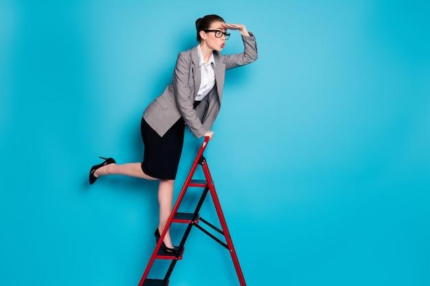 Zdjęcie profilowe o pełnej długości zdumiona dziewczyna agent trzymaj rękę oczy zegarek wspinaj się po drabinie nosić marynarkę czarna spódnica na białym tle niebieski kolor tła