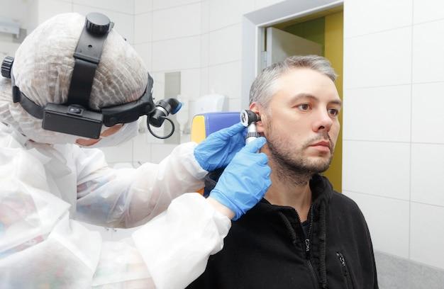 Zdjęcie profilowe otolaryngologa trzymającego otoskop przy uchu pacjenta podczas badania.