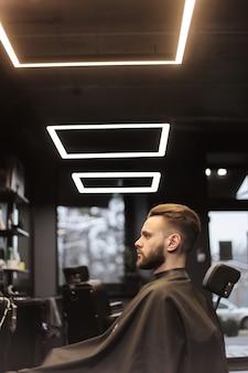 Zdjęcie profilowe pewnego siebie młodego mężczyzny, który patrzy w lustro, siedząc w fotelu u fryzjera.