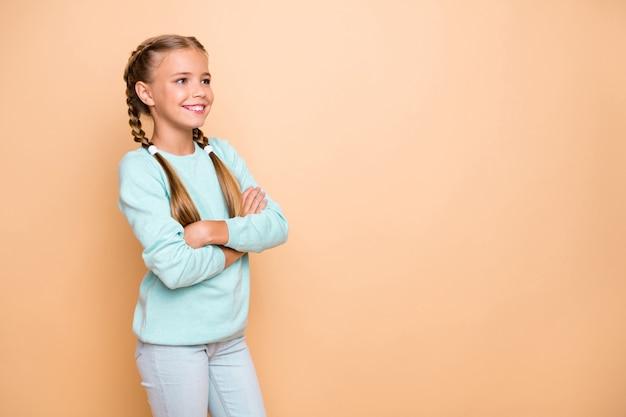 Zdjęcie profilowe pięknej, ładnej małej pani, skrzyżowane ramiona najlepszej uczennicy wyglądają po stronie pustej przestrzeni nosić niebieski sweter dżinsy na białym tle beżowy pastelowy kolor ściana