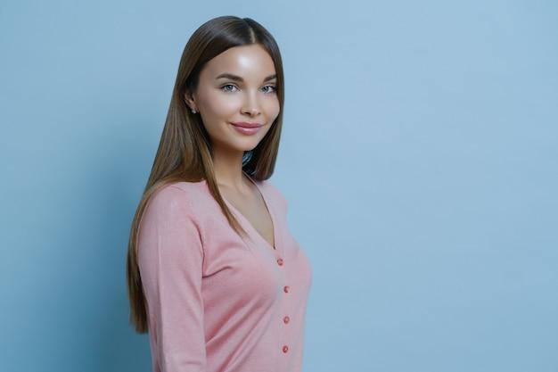 Zdjęcie profilowe pięknej uroczej brunetki ma długie proste włosy, nosi swobodny różowy sweter