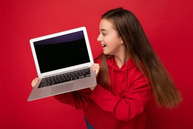 Zdjęcie profilowe po stronie pięknej dziewczyny szczęśliwy z długimi włosami na sobie czerwoną bluzę z kapturem, trzymając laptopa, patrząc na klawiaturę netbooka i ekran monitora na białym tle nad czerwoną ścianą. odetnij